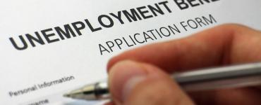 person filling out unemployment benefits form